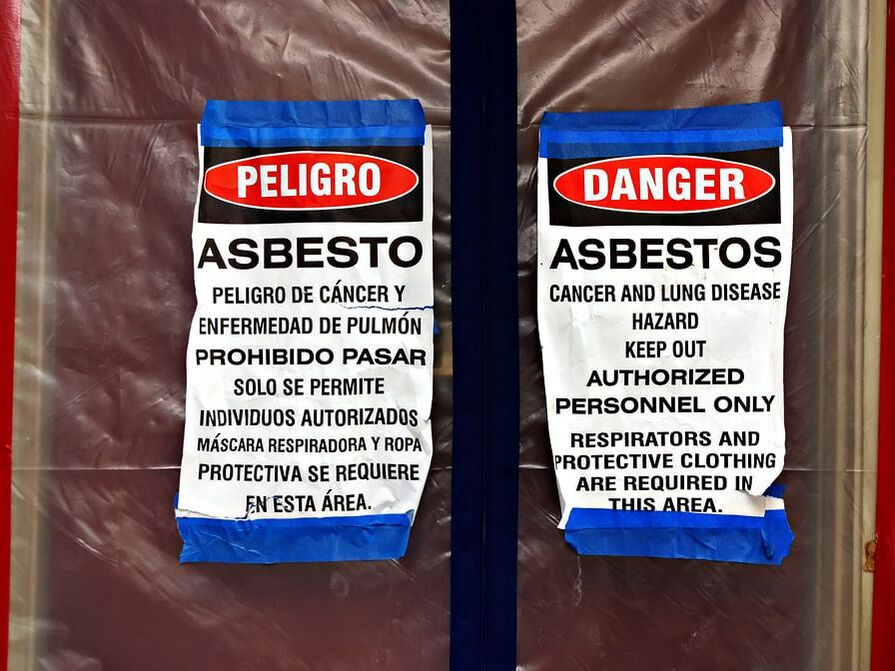 two danger signs asbestos being removed